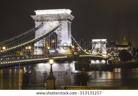 A night-time view of the historic Chain Bridge spanning over the River Danube in Budapest, Hungary.  St. Stephens Basilica can be seen in the distance. - stock photo