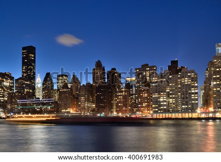 A night view of the New York City skyline from Roosevelt Island. - stock photo