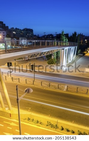A night view of the seaside bridge connecting the beach to GSO Sports park in Limassol, Cyprus. A view of the street, the wooden and glass pedestrian bridge, Fytideio sports park and paraliakos. - stock photo