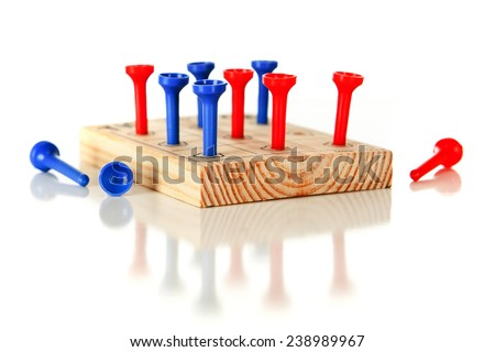 A nine-hole pegboard game with eight holes filled and three left over.  On a white background. - stock photo
