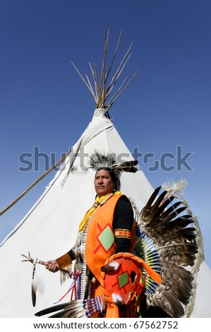 A Northern Cherokee indian in full ceremonial dress standing in front of a white tee pee. - stock photo