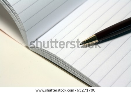 A note book and pen - stock photo
