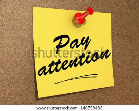 A note pinned to a cork board with the text Pay Attention. - stock photo