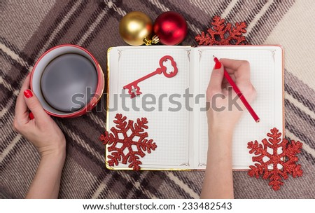 A notebook, a cup of coffee and Christmas decorations - stock photo