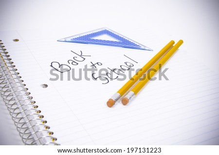 A notebook that has back to school on it, with a triangle, and two pencils. - stock photo