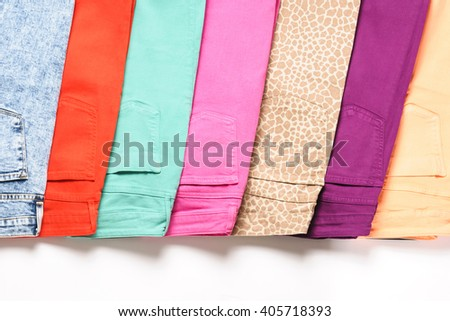 A number of colored jeans isolated on white background - stock photo