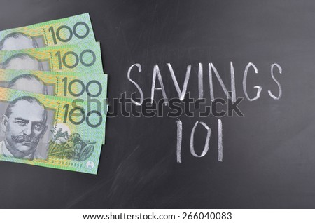 A number of one hundred Australian dollar notes on a blackboard where Savings is handwritten in white chalk - stock photo