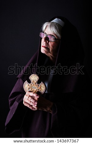 A nun looking up while holding a cross - stock photo