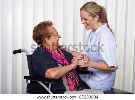 a nurse and an old woman in a wheelchair. - stock photo