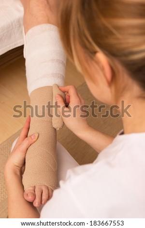 A nurse is applying a pressure bandage on a leg - stock photo