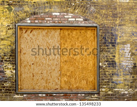 A old exterior brick wall with an old boarded up window ready for your content - stock photo