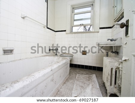A old, filthy white bathroom in an abandoned house - stock photo