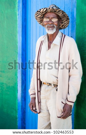 A old man standing in front of his colorful shack - stock photo