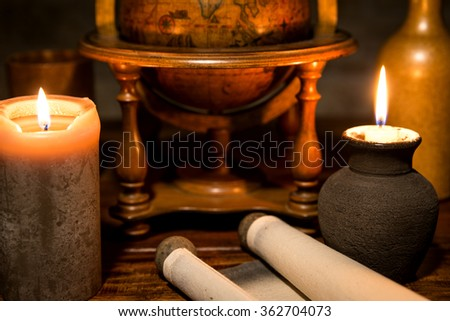 a old scroll with a globe and candles, concept adventure and traveling - stock photo