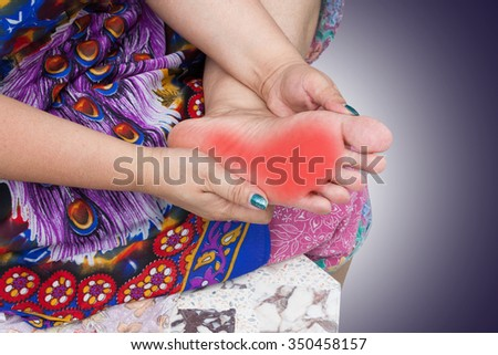 A old woman hands toching a aching foot - stock photo
