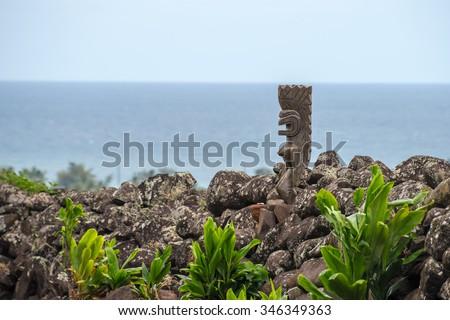 A old wooden Tiki god watches over sacred grounds on Kauai, Hawaii - stock photo