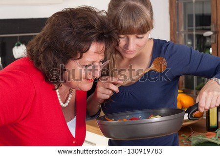 A older and a younger women are cooking in a kitchen and having fun - stock photo