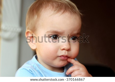 A one year blond boy looking aside musingly and thoughtfully and putting his finger on the mouth, close-up emotional portrait, indoor  - stock photo