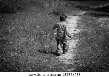 A one year old boy taking some of his first steps outdoors on a path.Vintage style photo with vignette  - stock photo