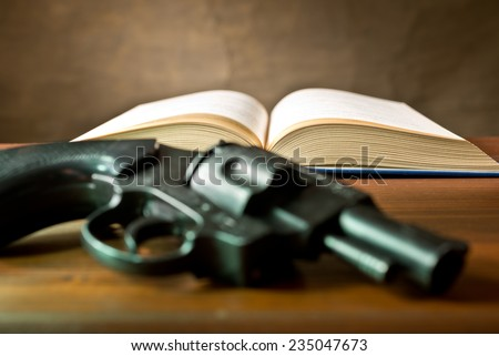 a open book and hundgun on the brown tablle - stock photo