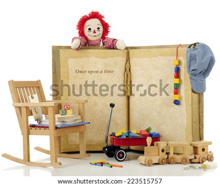 "A over-sized ""Once Upon a Time: book surrounded by vintage toys.  Focus on the words.  On a white background. - stock photo"