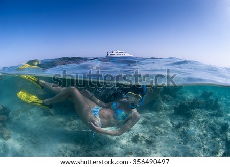 A over-under photograph of a fashion model in a tropical bikini and with yellow fins. The dive boat can be seen on the horizon against a blue sky.  - stock photo