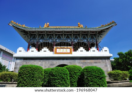 A pagoda and bushes under a clear blue sky. - stock photo