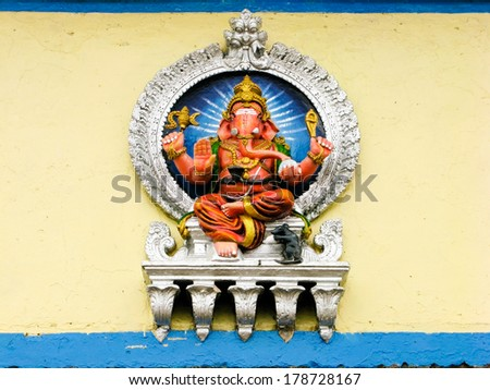 A painted sculpture of the Hindu god Ganesh on the wall of a temple. - stock photo