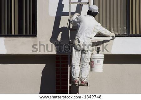 A painter applies a fresh coat of paint. - stock photo