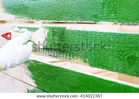a painter paints construction, paint brush with handle and dab of green paint , painting wooden furniture, close up, hand in protective cotton glove brush paints the wooden fence,  - stock photo