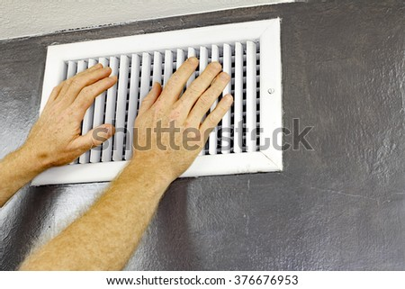 A pair of adult male hands feeling the flow of air coming out of an air vent on a wall near a ceiling. Man with hands in front of an air vent feeling for air flow. - stock photo