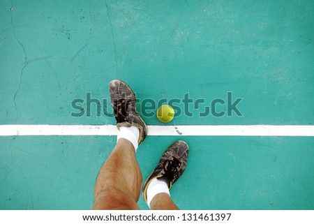 A pair of athlete feet standing on a tennis court baseline with a tennis ball. - stock photo