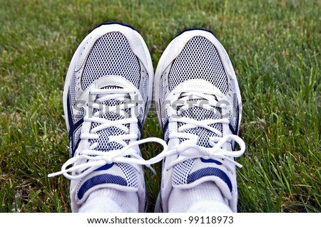 A pair of athletic shoes on a background of grass. - stock photo