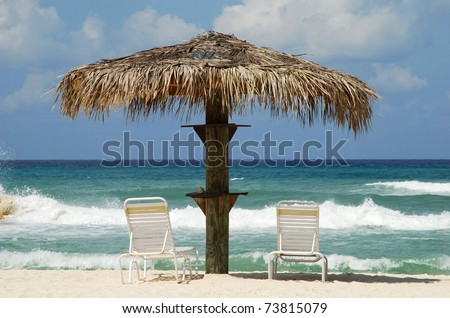 A pair of beach chairs with a perfect sea view on Grand Cayman Seven Mile Beach (Cayman Islands). - stock photo