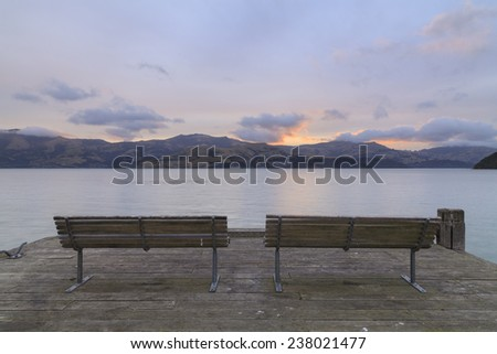 A pair of Benches at Wooden pier after sunset in Akaroa, Canterbury region, South Island, New Zealand. - stock photo