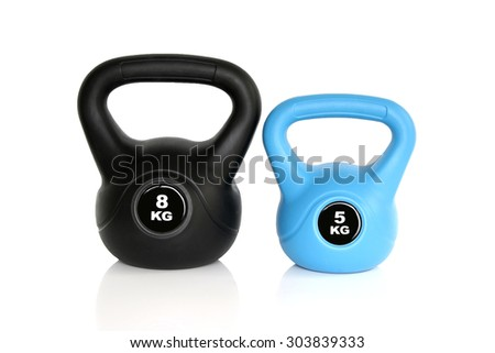 A pair of black 8 kg kettlebell and 5 kg blue kettlebell isolated on white background. Weights for a fitness training. - stock photo