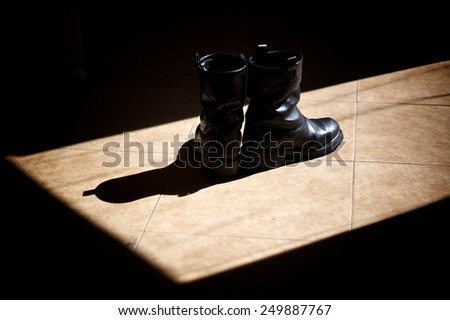 A pair of black leather biker boots standing on a tiled floor in the sunshine, surrounded by shadows. - stock photo
