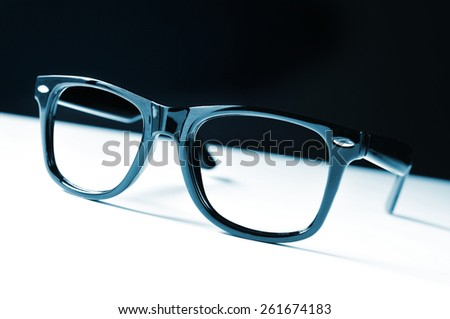 a pair of black plastic-rimmed eyeglasses on a white surface, and a black background - stock photo