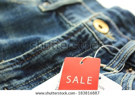 A pair of blue jeans with the sale tag on it. - stock photo