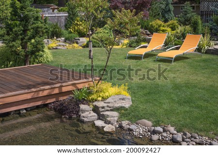 A pair of bright yellow designer lawn chairs invite you to relax in this beautifully landscaped backyard with deck spanning a creek in the foreground. - stock photo