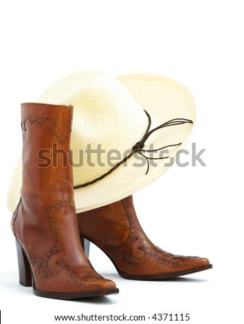 a pair of brown leather boots with a straw western hat - stock photo