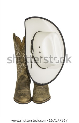 A pair of brown western boots and cowboy hat isolated on a white background - stock photo