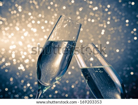 a pair of champagne flutes with golden bubbles make cheers on blue light bokeh background with space for text - stock photo