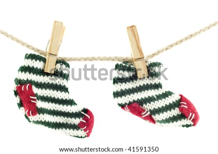 A pair of Christmas socks hanging on a clothes line, isolated on white with copy space, horizontal - stock photo