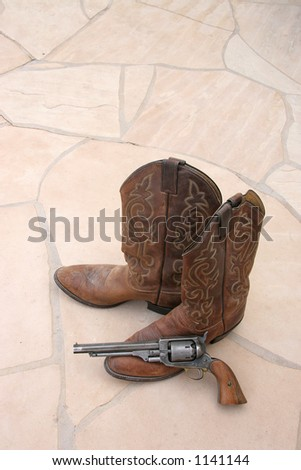 A pair of cowboy boots and a revolver on flagstone. - stock photo