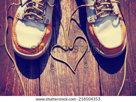 a pair of deck shoes on a nice wooden porch with the laces in a  - stock photo
