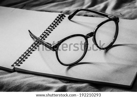 a pair of designer glasses on book,book with glasses - stock photo