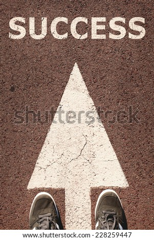 A pair of feet standing on street on white direction arrow. Success concept. Toned photo, low contrast. - stock photo