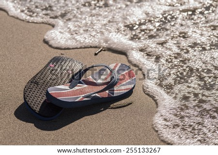 A pair of flip flop sitting on the beach during a sunset / Beach thongs - stock photo
