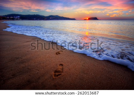 A pair of footprints arising from the tide flowing onto a beachy shore - stock photo